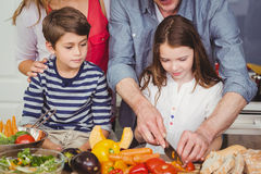 Father cutting vegetable with wife and children. In kitchen at home Stock Photos