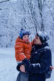 Father and his son playing outside, winter forest on the background, snowing, happy and joyful. Father, dad and his son playing outside, winter forest on the royalty free stock images