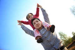 Father and daughter. On his shoulders against the blue sky Royalty Free Stock Photos