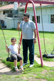 Father and daughter. A young smiling girl playing on the swings and having a good time with her father Stock Images