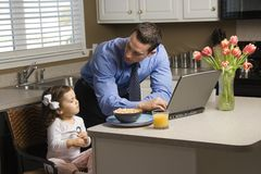 Father with daughter. Caucasian father in suit using laptop computer with daughter eating breakfast in kitchen stock images