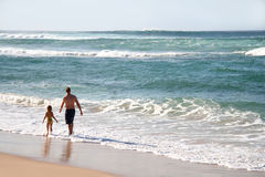 Father And Daughter. A man and his young daughter running along the beach Royalty Free Stock Photography
