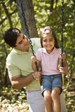 Father and daughter. Hispanic father pushing daughter on swing Royalty Free Stock Image