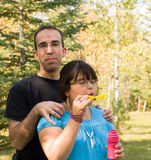 Father and Daughter. A young father standing behind his bubble blowing daughter Royalty Free Stock Image