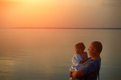 Father and daughter admiring the sunset on the lake royalty free stock images