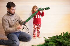 Father and daughter assembling christmas tree. Stock Images