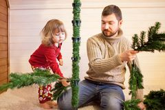 Father and daughter assembling christmas tree. Stock Photo