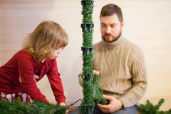 Father and daughter assembling christmas tree. Royalty Free Stock Images
