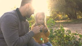 Father and daughter in the autumn park. Family holiday. Father and daughter are talking. The father shows a branch of a tree to a little girl. Joy of paternity stock video footage