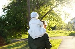 Father with daughter baby on shoulders walking away in park at sunny day. Family authentic portrait Royalty Free Stock Photo