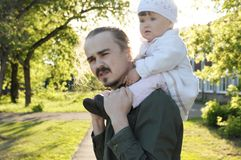 Father with daughter baby on shoulders walking in park at sunny day. Family authentic portrait Stock Photography