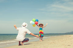 Father and daughter with balloons playing on the beach at the da Royalty Free Stock Images