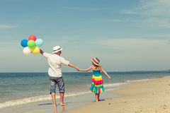 Father and daughter with balloons playing on the beach at the da Stock Images