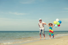 Father and daughter with balloons playing on the beach at the da Stock Image