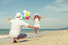 Father and daughter with balloons playing on the beach at the da Stock Photography