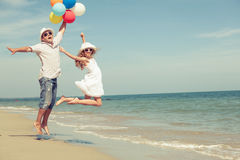 Father and daughter with balloons playing on the beach at the da Royalty Free Stock Photo