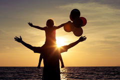 Father and daughter with balloons playing on the beach at the da Royalty Free Stock Image