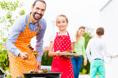 Father and daughter barbecue together Stock Photo