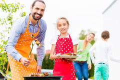 Father and daughter barbecue together Royalty Free Stock Photo