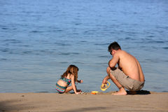 Father and daughter on the beach stock photography