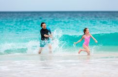 Father and daughter at beach. Father and his adorable daughter at beach having fun together royalty free stock photography