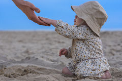 Father and daughter at the beach. Father reaching his hand to his daughter at the beach Royalty Free Stock Photos