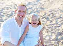 Father and daughter on the beach sand together Royalty Free Stock Image