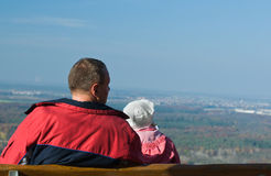 Father and daughter on a benc. H, looking at the  city Royalty Free Stock Images