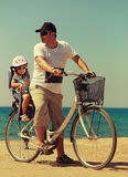 Father and daughter biking on the beach Stock Images