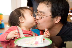 Father Daughter Birthday Kiss. Father kisses his daughter on her first birthday Royalty Free Stock Images