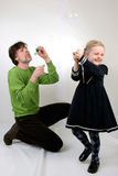 Father and Daughter blowing bubbles Stock Photos