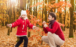 Father and daughter blowing bubbles outdoor in an autumn park. Smiling, cheerful father and daughter blowing soap bubbles and having fun outdoor in an autumn Stock Images