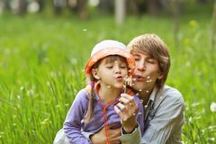 Father and daughter blowing on dandelions in a summer royalty free stock image