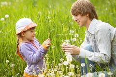 Father and daughter blowing on dandelions in a summer royalty free stock photos