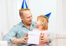 Father and daughter in blue hats with gift box Royalty Free Stock Image