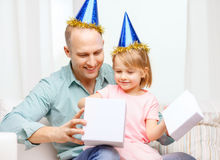 Father and daughter in blue hats with gift box Royalty Free Stock Photos