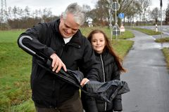 Father and daughter with broken umbrella royalty free stock image