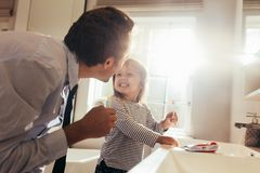 Father teaching daughter how to brush teeth. Father and daughter brushing teeth standing in bathroom and looking at each other. Man teaching his daughter how to royalty free stock photo