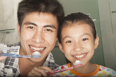 Father and Daughter Brushing Teeth Together Stock Photography