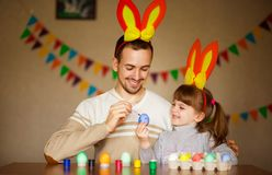 Father and daughter in bunny ears with colorful eggs in busket. Easter day. Modern Family preparing for Easter. stock image