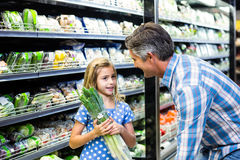 Father and daughter buying celery Royalty Free Stock Images
