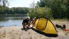 Father and daughter campers putting up tent. Happy travels concept, green tourism, hiking. Father and daughter campers putting up tent. Happy travels concept stock video footage