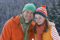 Father and daughter in cap and scarf smiling together outdoors Royalty Free Stock Images