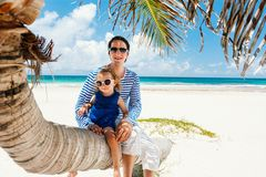 Father and daughter on Caribbean vacation. Father and daughter sitting on palm tree enjoying beach vacation royalty free stock photos