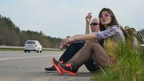 People sits on ground and catches the car hitchhiking. Father and daughter catching a car hitchhiking near the road. Two pleasant people sits on the ground near stock video