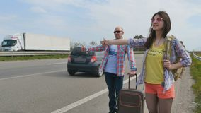Father and daughter catching a car hitchhiking near the road. Two pleasant people stands near the road and show a sign of thumb up. Young people traveling stock footage