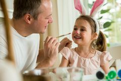 A father and daughter celebrating Easter, painting eggs with brush. royalty free stock image
