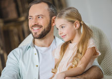 Father and daughter in chair. Smiling father and daughter sitting together in chair and looking away Stock Photography