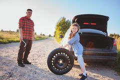 Father and daughter changing broken tire during summer rural road trip. stock photo