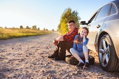 Father and daughter changing broken tire during summer rural road trip. stock photos